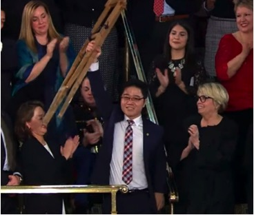 Ji Seong-ho, double amputee and North Korean defector raises his old crutches above his head at the State of The Union Address, January 30, 2018.